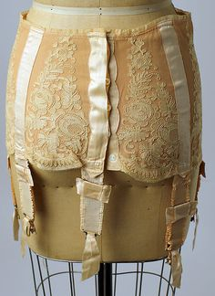 Corset: 928 silk, lace, rubber, steel, and mother-of-pearl French Corset. The corset became short and followed the changes in hemlines among dresses. This shorter length led to a greater demand for hosiery and stockings.