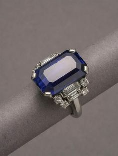 Platinum, Blue Sapphire and Diamond Ring. Set with a 14.30 carat elongated octagonal step-cut blue sapphire, flanked by four baguette-cut and eight round brilliant-cut diamonds.
