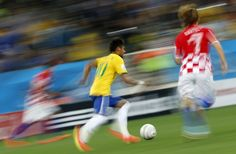 Brazil's forward Neymar (C) runs with the ball during a Group A football match between Brazil and Croatia at the Corinthians Arena in Sao Pa...