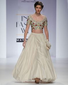Ivory Lehenga with fine pleats. This Lehenga comes with a matching short sleeves blouse featuring parsi and dabka embroidery in floral motifs adorning the bodice. Scoop neck. Wash Care: Dry clean onlyMatching plain dupatta includedBag used by the model is only for styling purposeDisclaimer: There might be a slight color variation in this item as this image is from the actual runway show.