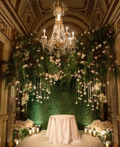 A beautiful chandelier and hanging flowers create an enchanted garden-inspired altar.
