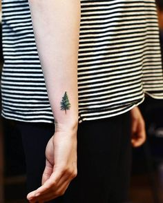 Pine tree tattoo on the right wrist.