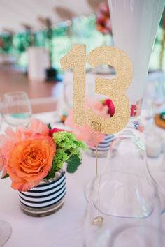 gold glitter table number detail with stripe ribbon and flowers at willowdale estate for a colorful summer reception