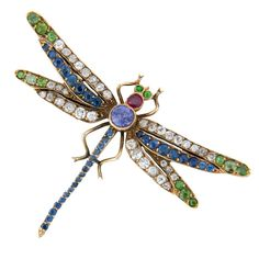 Art Nouveau Gem Set Gold Dragonfly Brooch. Circa 1910 yellow Gold Dragon Fly Brooch, very nicely detailed and centrally set with a Natural color change Purple sapphire further set with Demantoid Garnets. Diamonds, Ruby and Small sapphires. measures 2 1/4 inch from wing tip to wing tip. Obscured European hall marks. C 1910