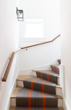 Kate Marker Interiors - Emily Kennedy Styling & Photography - A gray stair runner accented with orange stripes complements a two-toned staircase boasting stained wood treads and a stained wood handrail. White Staircase, Staircase Runner, Wood Staircase, Stairs, Wrought Iron Handrail, Wood Handrail, Railings, Black Wood Stain, Staircase Makeover
