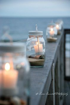 Mason jars made into lanterns with shells and sand