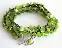 $24.99 The beads on this bracelet are tumbled/polished chips of lime colored Cat's Eye glass crocheted onto a polyester faux sinew cord with a silver-plated toggle clasp.