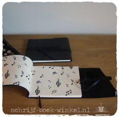 Zwart leren notitieboek of tekenboek, handgebonden met goed tekenpapier en papier met muzieknoten als schutbladen. Twee gemaakt, nog één beschikbaar. mail info@schrijf-boek-winkel.nl
