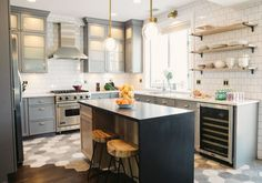 transitional kitchen wooden and tile floor concrete island metal and wood bar stools open shelves gray cabinets pendant lamps