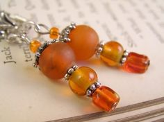 Orange glass dangle earrings. with Tibetan silver daisy spacers  by TheAmethystDragonfly, $16.50 USD