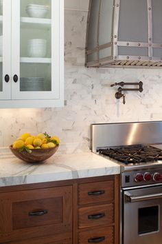 wood tone kitchen cabinets with marble or quartzite counter and white wall cabinets.