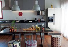 A cozinha deste apartamento de 70 m² decorada pela arquiteta Andrea Reis é cheia de personalidade. Pufes coloridos coordenados com cadeiras em volta da mesa de jantar servem de assento para amigos e família