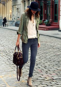 simple outfit: army green jacket, dark gray jeans, cream silk blouse, and booties. and a hat.