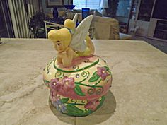 This is Tinkerbelle from Disney. This jar is really cute and would tickle some little girl. She is mint and has crystals all over. Painted brightly and really a great jar for your collections. Qualifies for many different collections actually.