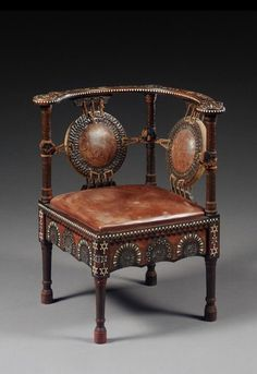 A walnut and inlaid corner chair by Carlo Bugatti, circa 1900 inlaid with pewter and ivory with later leather upholstered back and seat 72cm. high