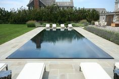 Disappearing pool pool beach style with patio furniture infinity pool purple flowers