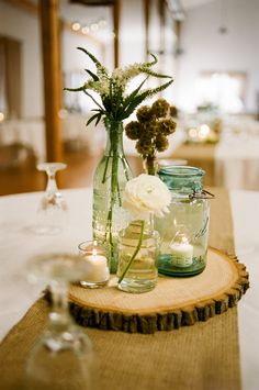 LOVE this rustic centerpiece with aqua antique mason jar, wood round and other miscellaneous vases