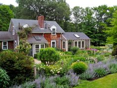 This formal cottage garden by Andrew Grosman is filled with beautiful blooms and features a pond framed by wetland plants and a gazebo in which to enjoy the surroundings.