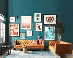 An artful living room // shop the style: modern chesterfield sofa - golden side table - floor lamp - blue rug - prints (l-r): colorful retro print - small bird print - large pink print - small geomatric print - autumn watercolor - pink and blue print...