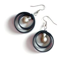 Unique circle swirl earrings made from black rubber upcycled bicycle tire innertube and white freshwater pearls. Recycled black and white
