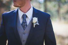 Groom in blue suit, gray vest, paisley tie. Lavender boutonnière