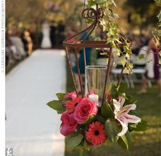 Wrought iron lanterns decorated with Gerbera daisies, roses and lilies hung from shepherd hooks covered in ivy to mark the aisle.