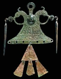 CELTIC BRONZE PENDANT Circa 400 B.C. The thin, cast pendant triangular in form, the raised central boss with a stylized human face flanked by horse heads with projecting loops, each supporting an elongated drop, and a central loop above, the surface with stamped dotted circles and bands of hatching, the lower edge with seven perforations, one preserving sheet pendants with dotted circles  6 in. (15.2 cm) long.  Sold at Christie's; no country of origin listed.