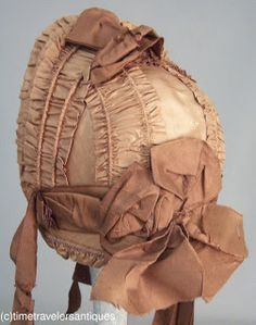 "Circa 1862 Civil War era girl's golden brown silk taffeta spoon bonnet drawn over natural cane, buckram, and wired foundation, complementing taffeta bows, chin ties, and streamers, with cloth flowers to the under brim, and a buckram lining. 10"" tall and 7"" across the face."