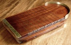 Sworders - Fine Art Auctioneers - A George III shove ha'penny board, with brass fittings and hinged dividers 35cm wide 60cm long