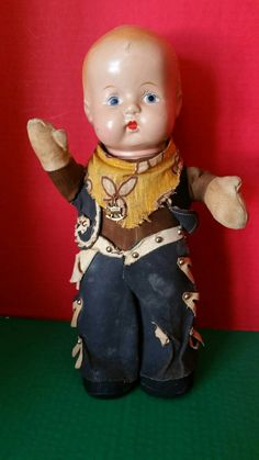Antique Composition Cowboy. This cutie stands on his own at aprox. 14 inches. Body is made of cloth. He has his original outfit and pin.
