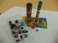 Amb una base de cartró, dos tubs, boletes i anelles de diferent mida, treballem la concentració i la motricitat fina.  Con una base de cartón, dos tubos, bolas y anillas de diferente medida, trabajamos la concentración y la motricidad fina.