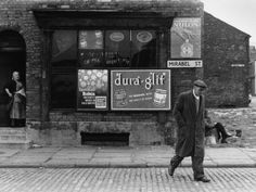 © Shirley Baker Old Man Walking Away from Grocers Shop