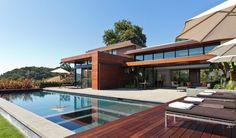 piscine contemporaine: plage bois, dallage et parterres exotiques