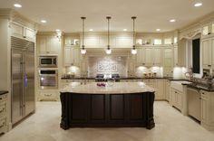 travertine floors, dark kitchen island, lighter outside cabinets, stainless steel