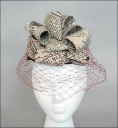 Circa 1966 Bes-Ben 'Newsprint' hat | United States | Three-inch wide loops of black and white newsprint patterned fabric entirely cover the crown of small hat edged with black beads. Red veil.
