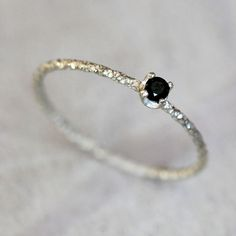 Black diamond solitaire ring. The sweetest little black diamonds sits atop a faceted sterling silver wire band. The perfect engagement ring for that one of a kind bride. The ring is delicate and preci