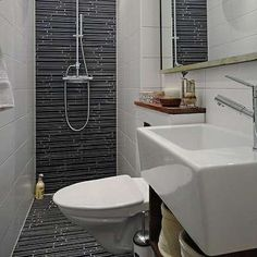 SMALL SPACE, GREAT BATHROOM: This bathroom is mostly unadorned, apart from one striking design element—the tile. The black linear tile ascends from the floor up the back wall of the shower, creating a streamlined, modern look.