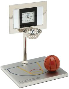 """Silver Basketball Court Clock Size: 3"""" x 4"""" Give a """"Slam Dunk"""" present by gifting the Basketball Court Clock. The Basketball Court Clock is an impressionable souvenir for lovers of the sport. The basketball hoop clock has a clock on the backboard which makes a great desk accessory for the home or office as it keeps you in time to watch your team's playoff game. Call a basketball court your own by personalizing your name or favorite phrase on the base of the clock. The Basketball…"""