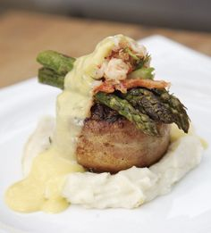 Steak Oscar Burger is a bacon-wrapped beef tenderloin burger topped with lump crabmeat, asparagus and dijon mustard sauce.