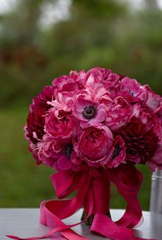 """Brides Magazine: Unique Wedding Flower Ideas  - Stunning Centerpiece    A monochromatic bouquet in a vibrant mix of """"Yves Piaget"""" roses, nerines, dahlias, and anemones doubles as a festive reception centerpiece. If the stems are cut evenly, it can be stabilized with a pin frog (a heavy metal disc with a spiky top, available at floral-supply stores)."""
