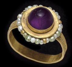 A BYZANTINE GOLD, PEARL AND AMETHYST FINGER RING  CIRCA 6TH-7TH CENTURY A.D.  The exterior of the strap hoop ornamented with braided plain wire filigree, the sides of the spool-shaped bezel with a ring of pearls threaded on a wire and secured by small loops, bands of beaded wire above and below, the bezel set with a circular cabochon amethyst