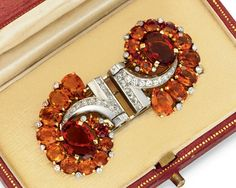 A RETRO CITRINE AND DIAMOND DOUBLE-CLIP BROOCH, BY CARTIER   Each centering upon a reddish-orange oval-cut citrine, within a graduated pear-shaped, oval and circular-cut citrine surround, with collet-set diamonds, enhanced by circular and square-cut diamond scrolling geometric detail, mounted in platinum and gold, (accompanied by a white gold pin attachment, with French importation marks), circa 1940