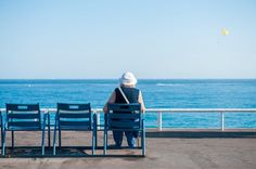 An old lady sits for a moment on one of the blue chairs of Nice on the Promenade des Anglais and follow the parasailing passing off.