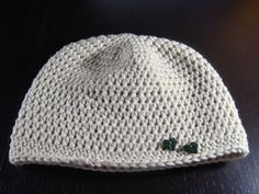 gehäkelte naturfarbene Mütze mit zwei dunkelgrünen Herzknöpfen