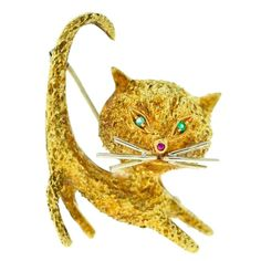 Gorgeous Yellow Gold Stretching Cat Pin with Emerald Eyes | From a unique collection of vintage brooches at https://www.1stdibs.com/jewelry/brooches/brooches/
