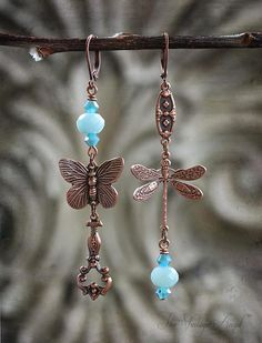 Asymmetrical whimsy in aged copper paired with Amazonite gemstone beads and Swarovski bicones.  Dragonflies and butterflies dance and play with this unique pair of asymmetrical earrings with leverback hooks for pierced ears.    Antique copper leverback hooks, components are antique copper plated brass (lead and nickel free)   Lightweight and easy to wear   Comes beautifully gift boxed   A little over 2.75 inches long including hooks.