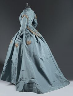 """Robe de ville in grey-blue (""""bleu petrole"""") ottoman (rib silk?), c. 1865 Bodice has short coat-tails, lovely skirt over crinoline,belt w/rosette en tissu forming streamers pleated and fringed w/silk. Borders, sleeves, waist trimmed w cream fringe Superbly concerved Registry printed with gold ribbon """"Madame Roger."""" http://www.thierrydemaigret.com/flash/index.jsp?id=22004&idCp=90&lng=fr&npp=10000"""