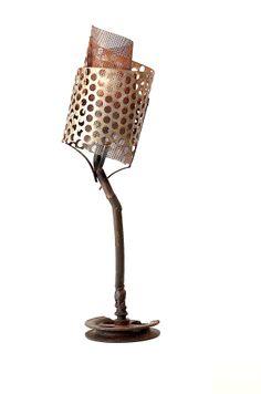 Concha Perfurada  Descrição: luminária de mesa com cúpula de tela perfurada, projetando um desenho de sombras que se movimenta conforme o ângulo de observação.  Técnica: duas telas de chapas perfuradas enroladas em forma de espiral, pé feito com pedaços de tubos, uma roldana de ferro fundido e pintura com verniz fosco.  Peso: 5 kg Dimensão: 35 x 48 cm