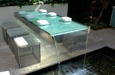 Glass table with running water, looks cool but probably makes you pee more often when you are having dinner with friends.: