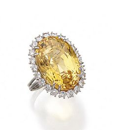YELLOW SAPPHIRE AND DIAMOND RING, HARRY WINSTON.  The oval-shaped yellow sapphire weighing 37.87 carats, surrounded by 22 round diamonds weighing approximately 2.20 carats, mounted in platinum